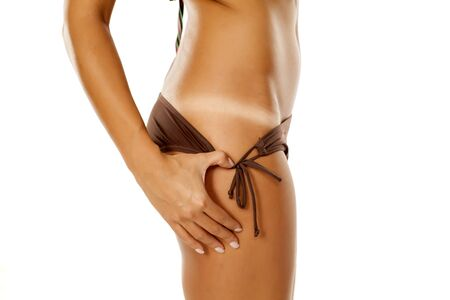 woman pulls her panties and shows her tanned skin