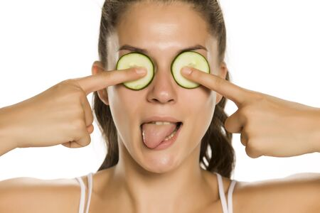 Young funny woman posing with slices of cucumbers on her eyes on white background