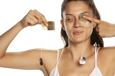 Young smiling woman posing with tea bag on her eye on white background Stok Fotoğraf