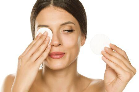 Giovane bella donna che si strofina il viso con un batuffolo di cotone su sfondo bianco
