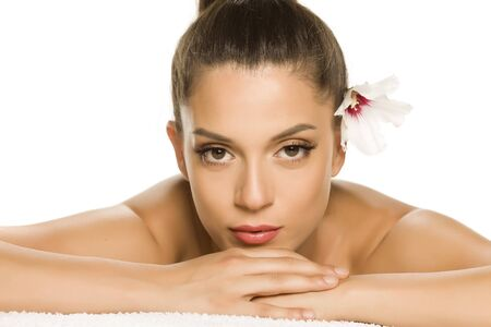 Sensual portrait of a young beautiful woman with flower on her hair, lying on a white background