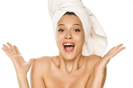 Young beautiful happy woman with towel on her head on white background