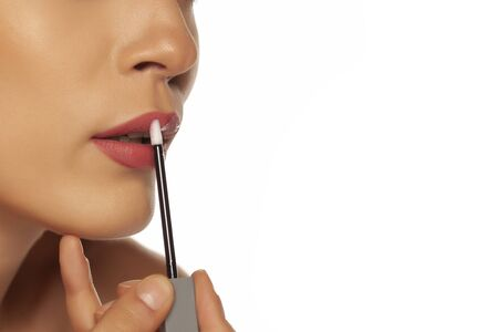 closeup of  woman applying lipgloss on white background