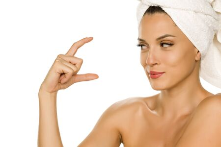 Young beautiful advertizing woman with towel on her head on white background