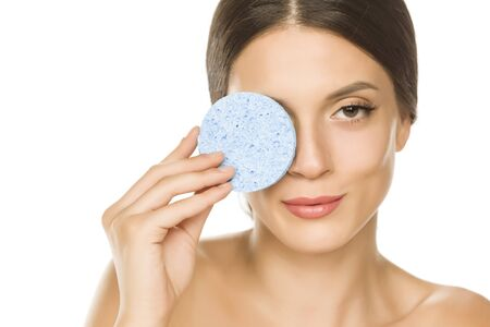 young beautiful woman posing with a sponge pad on the white background