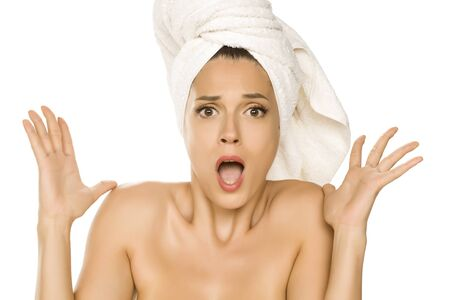Young beautiful shocked woman with towel on her head on white background