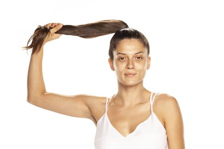 Young woman without makeup, holding her panytail on white background