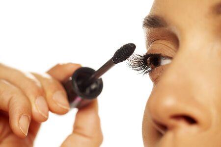 closeup of woman applying mascara on her eyelashes