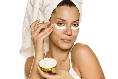 Young woman applying face cream under heer eyes on white background Stok Fotoğraf