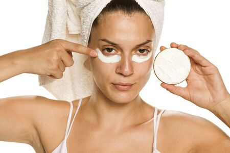 Young woman applying face cream under her eyes on white background Stok Fotoğraf