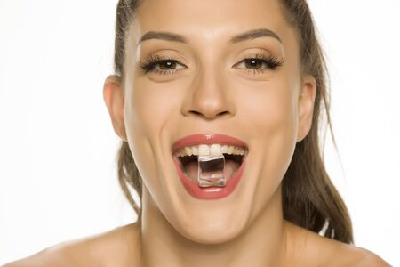 young beautiful woman holding ice cube in her mouth on white background