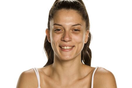 Young smiling woman without makeup on white background