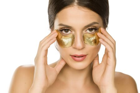 Young beautiful woman posing with golden patches under her eyes on white background Stok Fotoğraf