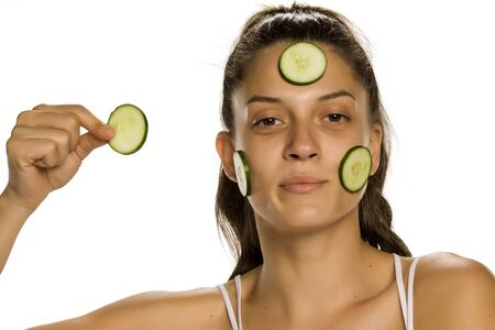 Young smiling woman posing with slices of cucumbers on her eyes on white background