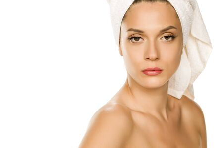 Young beautiful woman with towel on her head on white background