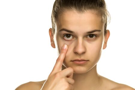 Young woman pulling her lower eyelid with her finger on white background