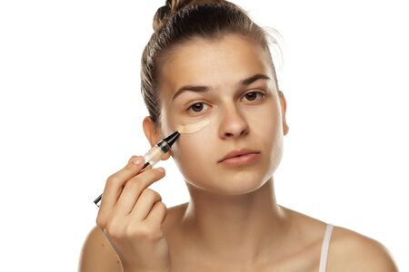 Portrait of young woman applying concealer with brush on white background Banco de Imagens