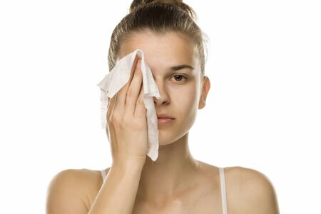 Young woman cleaning her face with wet wipe on white background Reklamní fotografie
