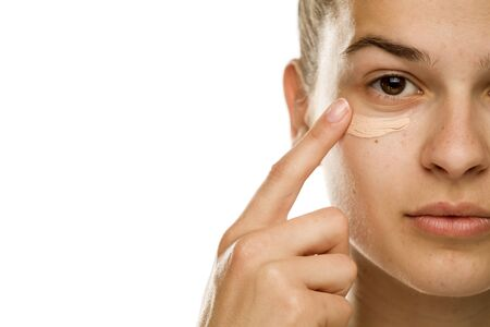 Portrait of young woman applying concealer with her finger on white background