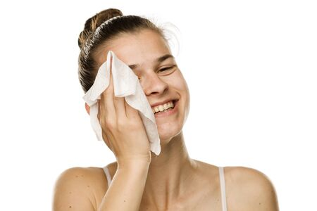 Young happy woman cleaning her face with wet wipe on white background
