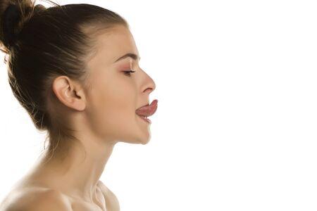 Giovane donna che cerca di toccare il naso con il suo tougue su sfondo bianco