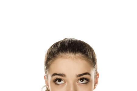 Young confused woman looking up on white background