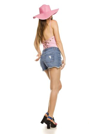Young lady with hat and shorts posing on white background