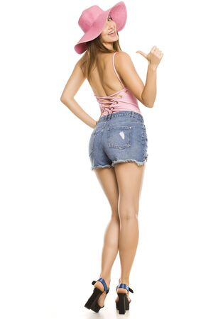 Young happy lady with hat and shorts posing on white background and showing thumbs up