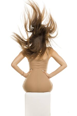 Back view of young lady in dress and long flying hair posing on white background