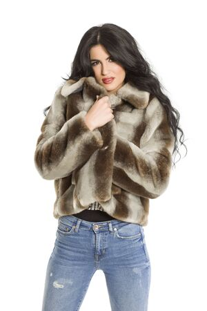 Attractive woman in fur jacket posing on white background