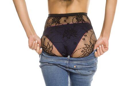 Eine Frau zieht ihre engen Jeans auf weißem Hintergrund an
