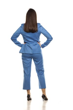 Back view of young business woman standing on white background Banque d'images