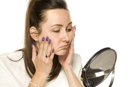 bored woman looking at herself in the mirror on white background