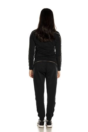 Back view of young woman in black track suit posing on white background
