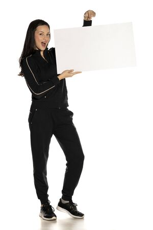 Young smiling woman in black track suit holding empty white board on white background
