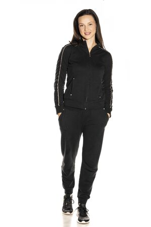 Young woman in black track suit posing on white background Foto de archivo