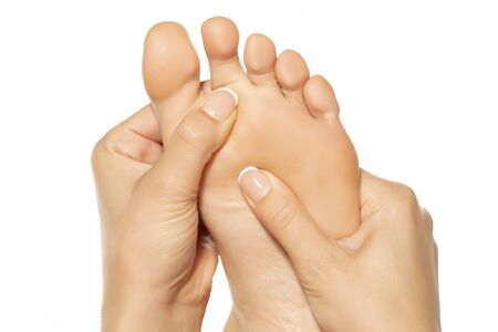 woman massaging her painful foot on white background Foto de archivo
