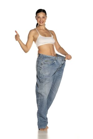 Young slim woman in big size pants showing thumbs up on white background