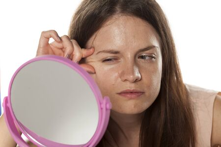 young woman without make-up looks at mirror her wrinkles