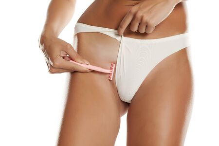 Woman with panties shave her pubic hair on white background Stock fotó
