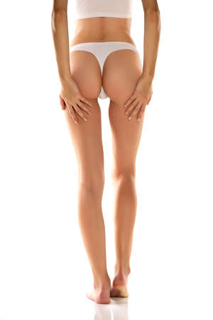Back view of young woman's legs and bottom in white thong on white background