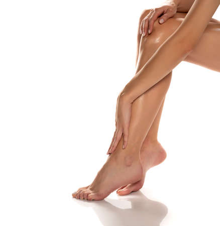 woman applying lotion on her legs on white background