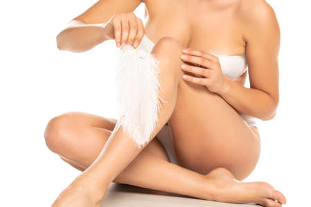 woman touches her smooth legs with feather on white background