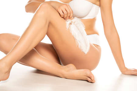 woman touches her smooth legs with white feather