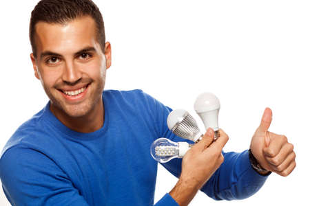 portrait of happy young man, holding three different LED bulbs on white background and showing thumbs up