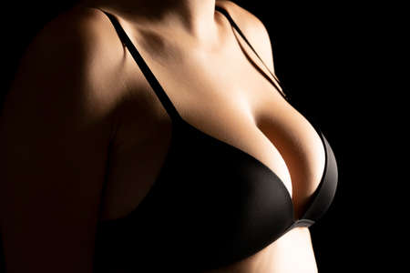 Woman with perfect breasts in black bra on black background