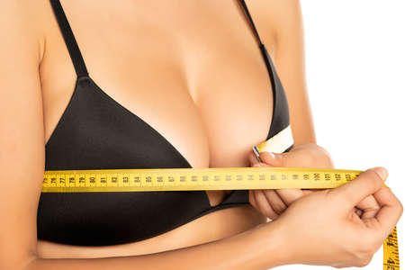 Woman measures her breasts with mettering tape