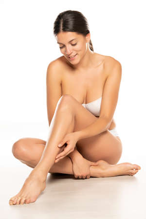 Happy woman touches her smooth legs on white background