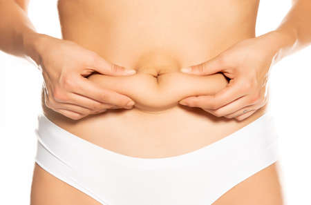 Woman pinching her belly fat on white background Standard-Bild