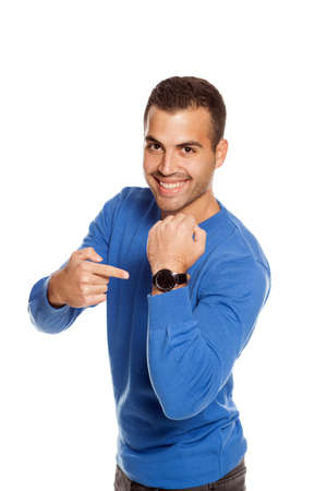 handsome smiling young man in blouse pointing on his wrist watch  on white background Standard-Bild